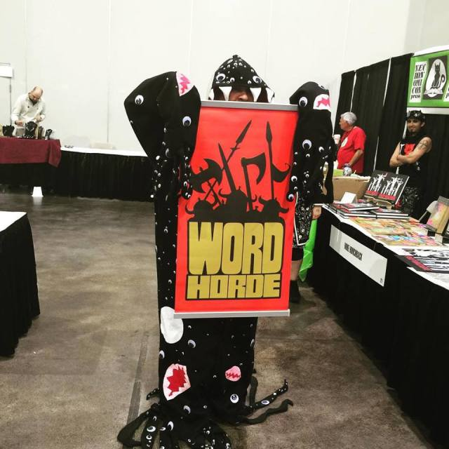 Matthew Warren Richey carrying the Word Horde banner in the dealer room